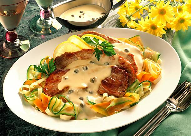 Schnitzel on colorful vegetables with ribbon noodles